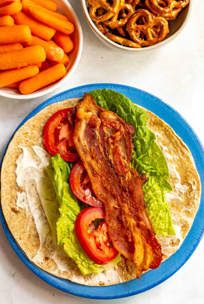Whole wheat BLT wrap with bowls of carrots and pretzels in the background