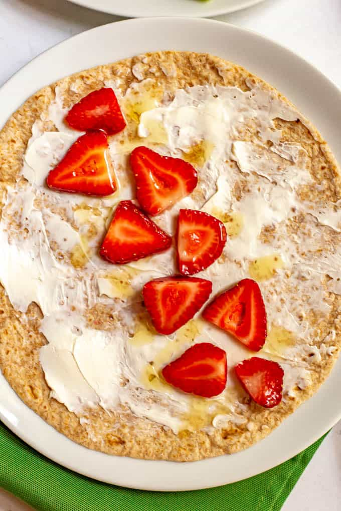 Whole wheat wrap with cream cheese, sliced strawberries and a honey drizzle