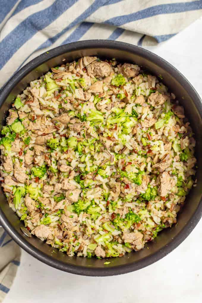 A large pot with cooked wild rice, broccoli and turkey sausage all mixed together