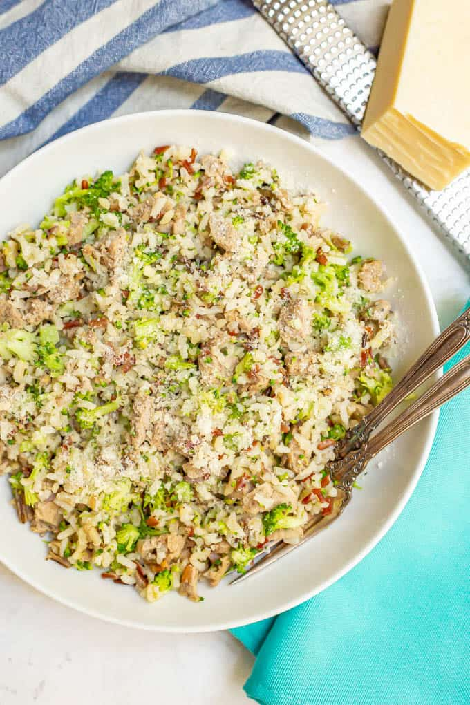 Bowl of wild rice with turkey sausage and broccoli all mixed together with Parmesan cheese on top and two forks alongside