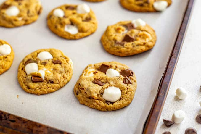 Close up of a baked cookie with chocolate and marshmallows on a baking sheet