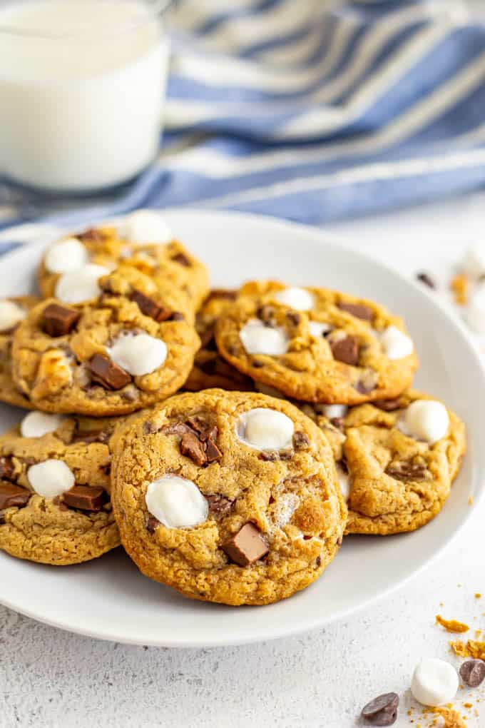 S'mores cookies served on a white plate with a blue towel and a glass of milk in the background