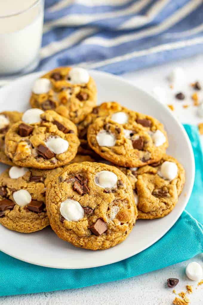 A white plate full of chocolate chip cookies with marshmallows and a glass of milk in the background