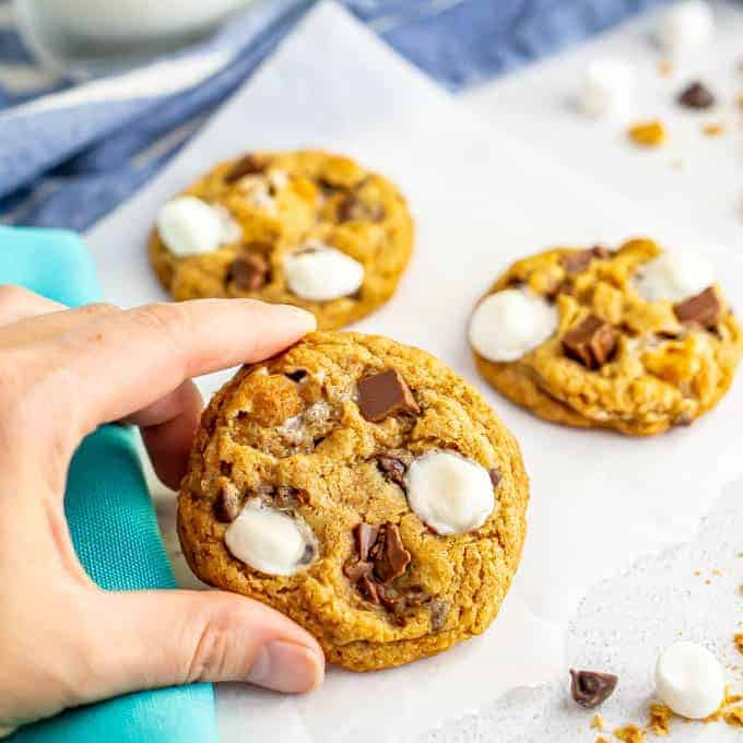 A hand holding a cookie with mini marshmallows and chocolate chunks on top