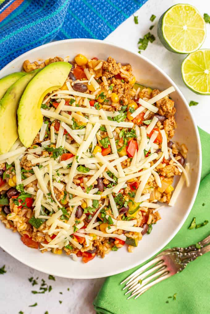 Bowl of ground turkey, rice, beans and veggies with cheese, cilantro and avocado served with two forks and limes nearby