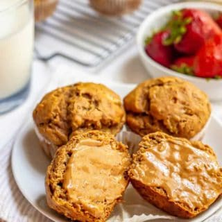 Muffins on a plate with one cut in half and smeared with peanut butter