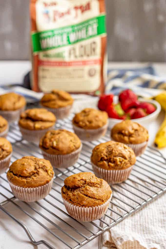 Healthy peanut butter banana muffins on a cooling rack with a bag of flour in the background
