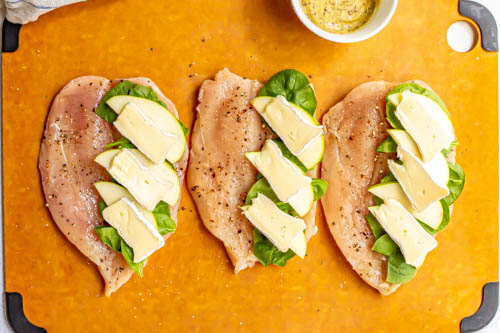 Butterflied chicken breasts on a cutting board with spinach, apples and brie slices on top