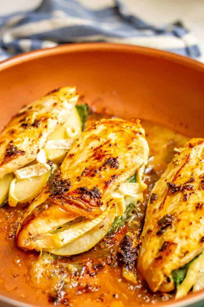 Pan seared chicken breasts with cheese and apples in a large skillet