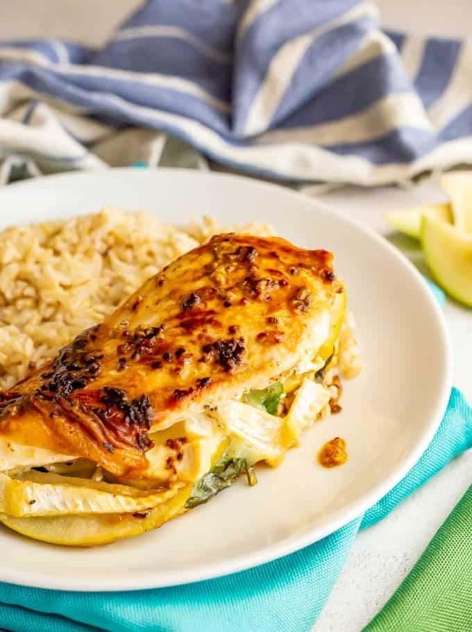 A mustard coated chicken breast with apples and brie served on a white plate with rice