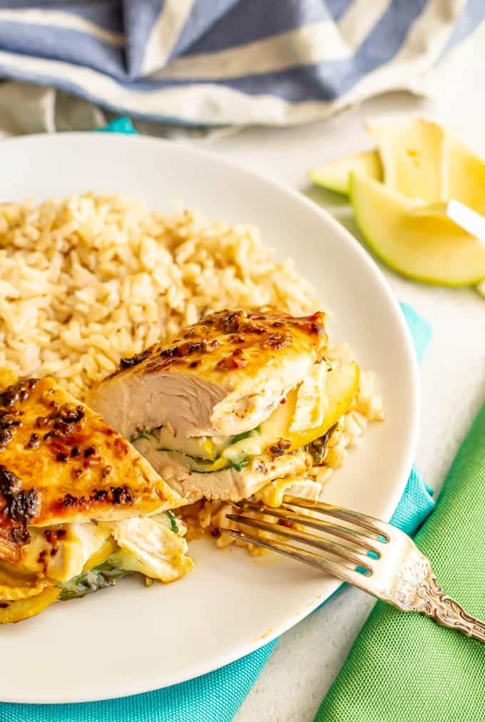 Chicken breast stuffed with spinach, apple and brie cheese cut in half on a white plate with rice alongside it