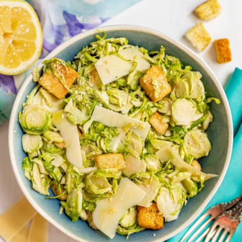 A serving bowl filled with Brussel sprout Caesar salad with a lemon, Parmesan cheese and croutons scattered nearby