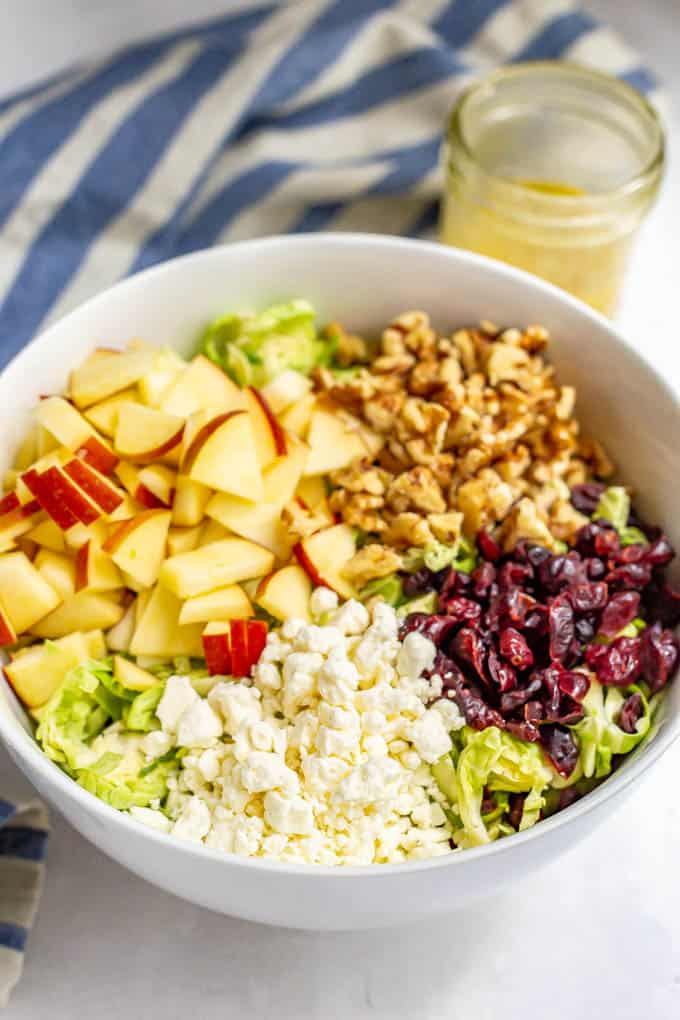 Salad bowl with salad ingredients arranged separately, including chopped apples, walnuts, dried cranberries and feta cheese