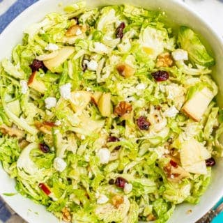 Shaved Brussel sprout salad with apples, walnuts, dried cranberries and feta in a large bowl with towels and napkins nearby