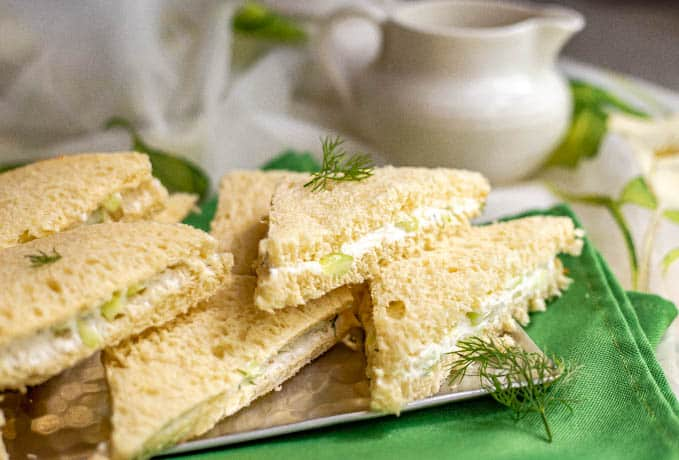Mini triangle sandwiches stacked on each other on a silver serving tray with a teapot in the background