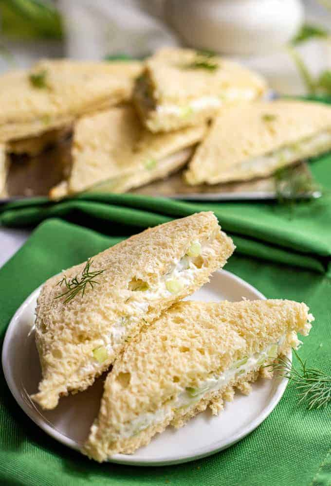 Cucumber tea sandwiches stacked on a small white serving plate with green napkins underneath