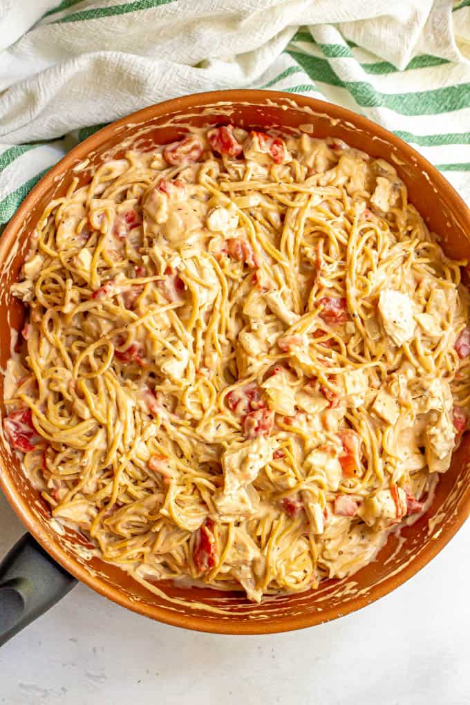 Spaghetti with chicken, tomatoes and a creamy sauce mixed together in a large pan