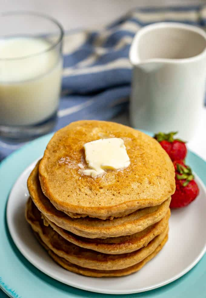 Stack of homemade pancakes with a pat of butter on top served on a white plate with strawberries