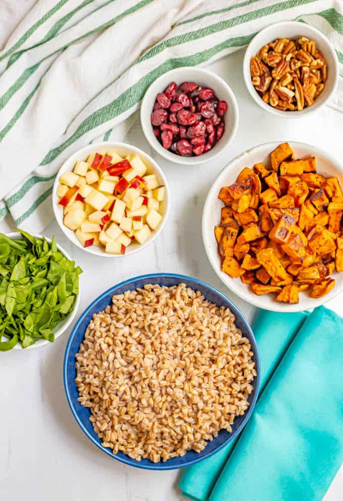 Ingredients prepped in separate bowls, including farro, roasted sweet potatoes, spinach, apples, pecans and dried cranberries