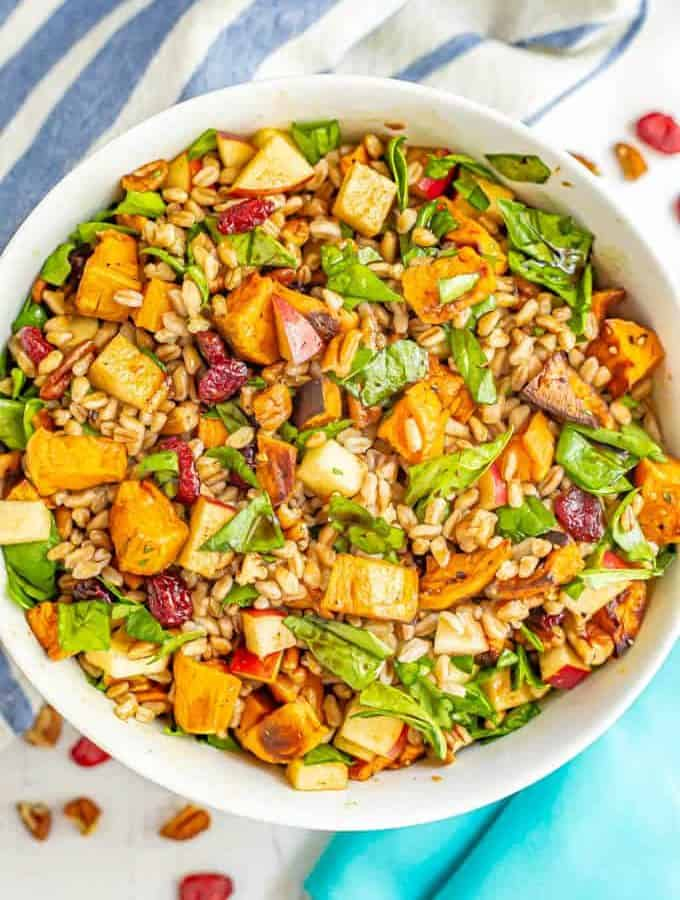 A harvest farro salad with sweet potatoes, spinach, pecans and apples in a large white bowl