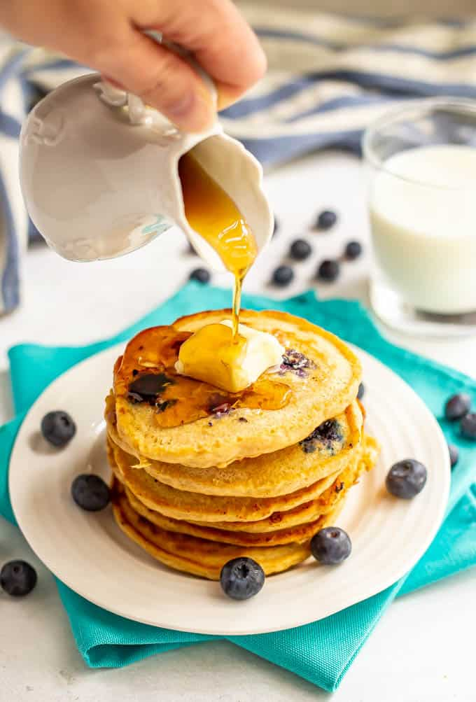 Maple syrup being poured over a stack of blueberry pancakes with blueberries scattered nearby