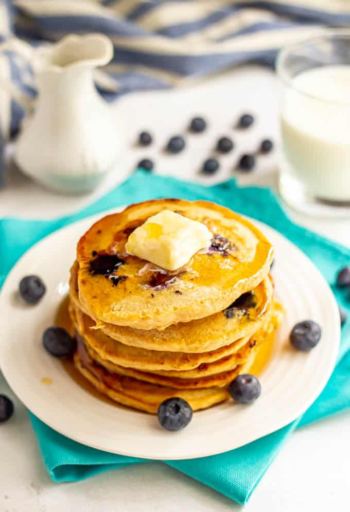 A stack of healthy blueberry pancakes with a pat of butter on top and a drizzle of maple syrup