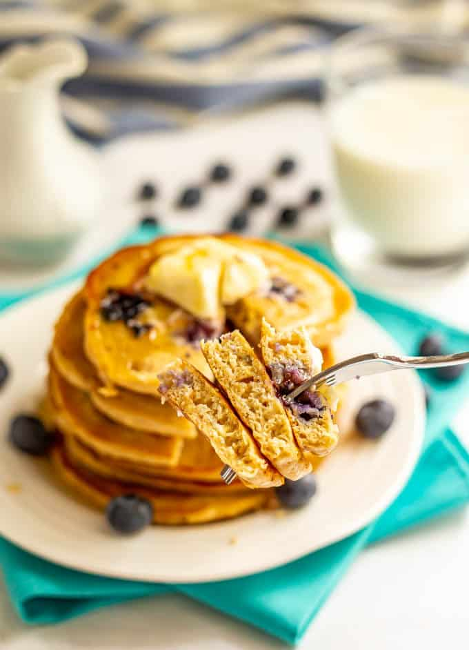 A forkful of blueberry pancakes being held up