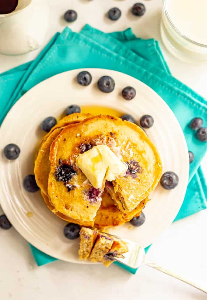 A top down shot of a stack of blueberry pancakes with butter and maple syrup and a forkful bite laying to the side