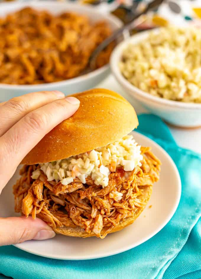 Hand picking up a BBQ pulled pork sandwich with coleslaw