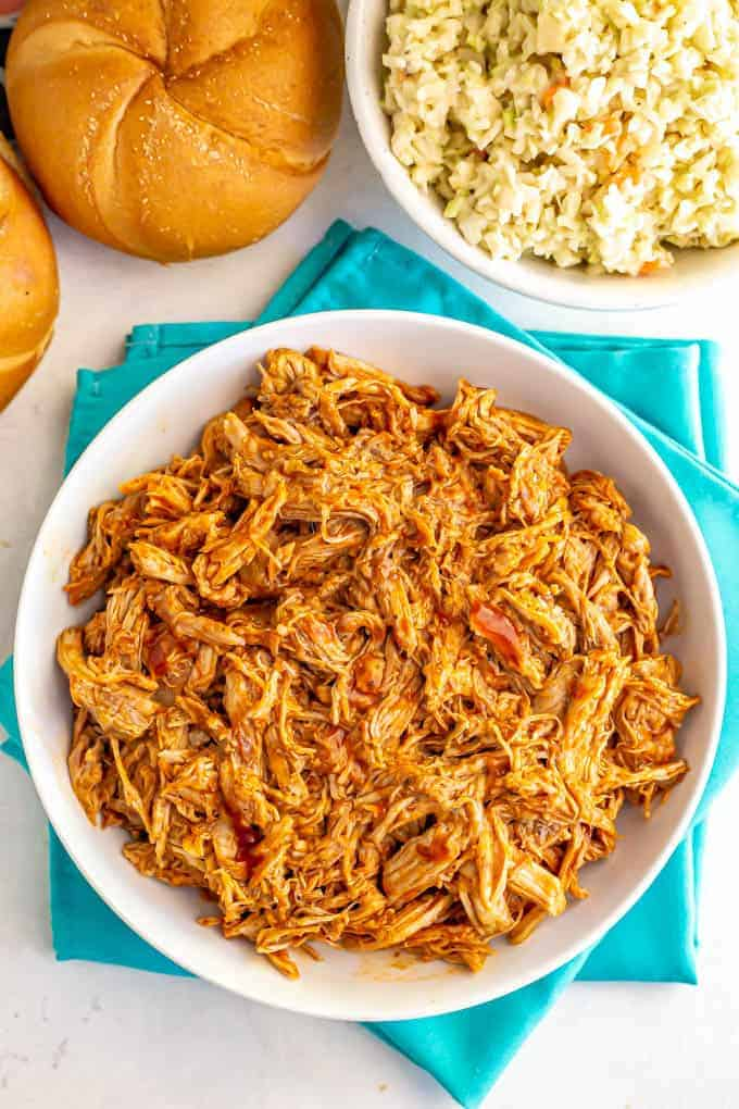 Large white bowl of shredded Instant Pot pulled pork with BBQ sauce and a side of coleslaw