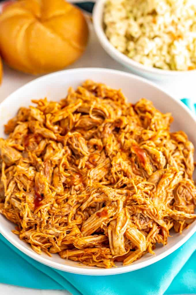 Large white bowl of shredded Instant Pot pulled pork with BBQ sauce