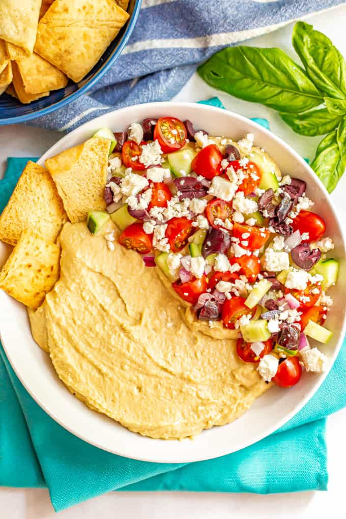 Hummus dip appetizer with chopped fresh veggies, feta cheese and pita chips for serving
