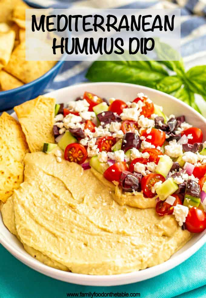 Mediterranean layered hummus dip is creamy, colorful and loaded with fresh flavors. This easy appetizer is quick to put together, can be made ahead and goes great with pita chips! #hummus #appetizer #mediterraneanfood #hummusdip #partyfood #gamedayeats