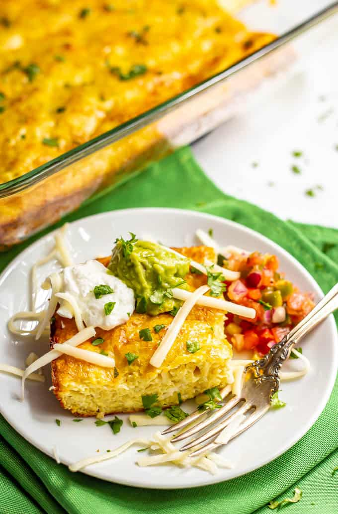 A slice of cheesy Mexican baked eggs served on a plate with toppings and a fork to the side