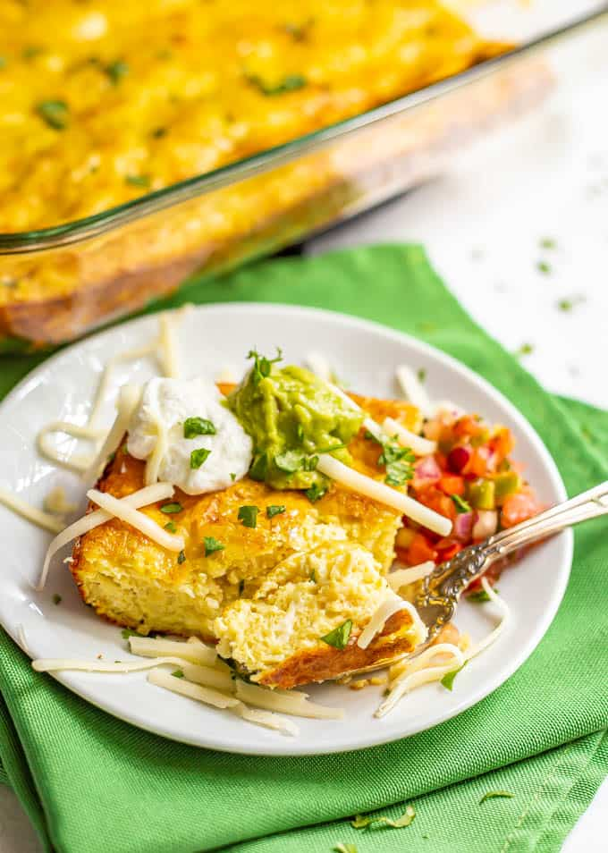 A slice of cheesy Mexican baked eggs served on a plate with toppings and a fork