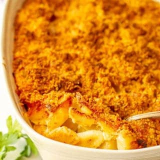 Baked macaroni and cheese casserole with a spoonful being taken out