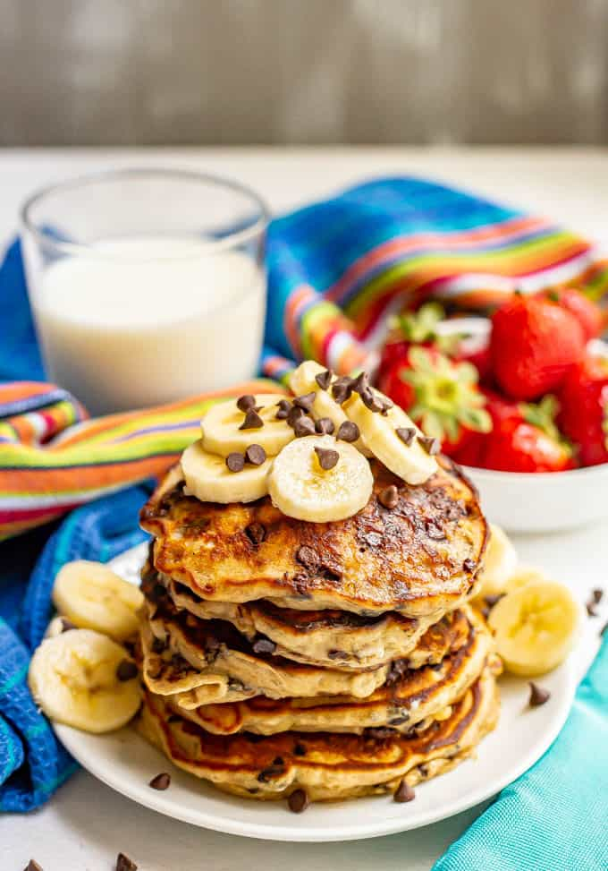 A stack of freshly made banana chocolate chip pancakes served with extra bananas and chocolate chips on top