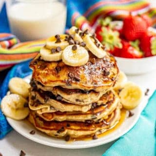 A stack of fluffy banana chocolate chip pancakes served with sliced bananas, mini chocolate chips and maple syrup