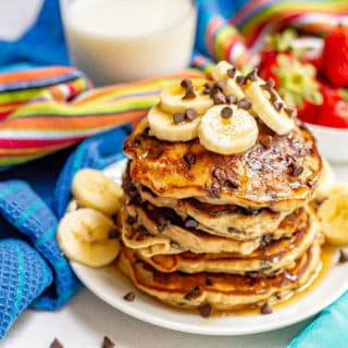 A stack of fluffy pancakes with chocolate chips served on a white plate with bananas and maple syrup