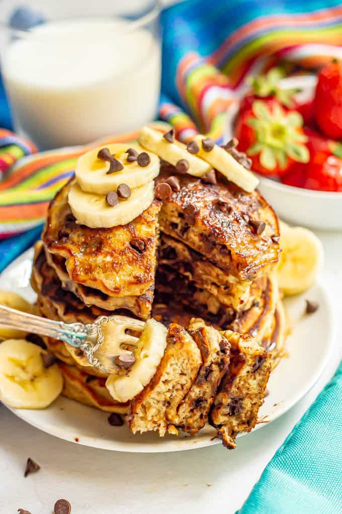 A forkful of pancakes with chocolate chips and banana being taken from a stack on a white plate