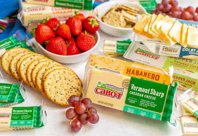 Spread of Cabot cheeses with fresh fruit and crackers