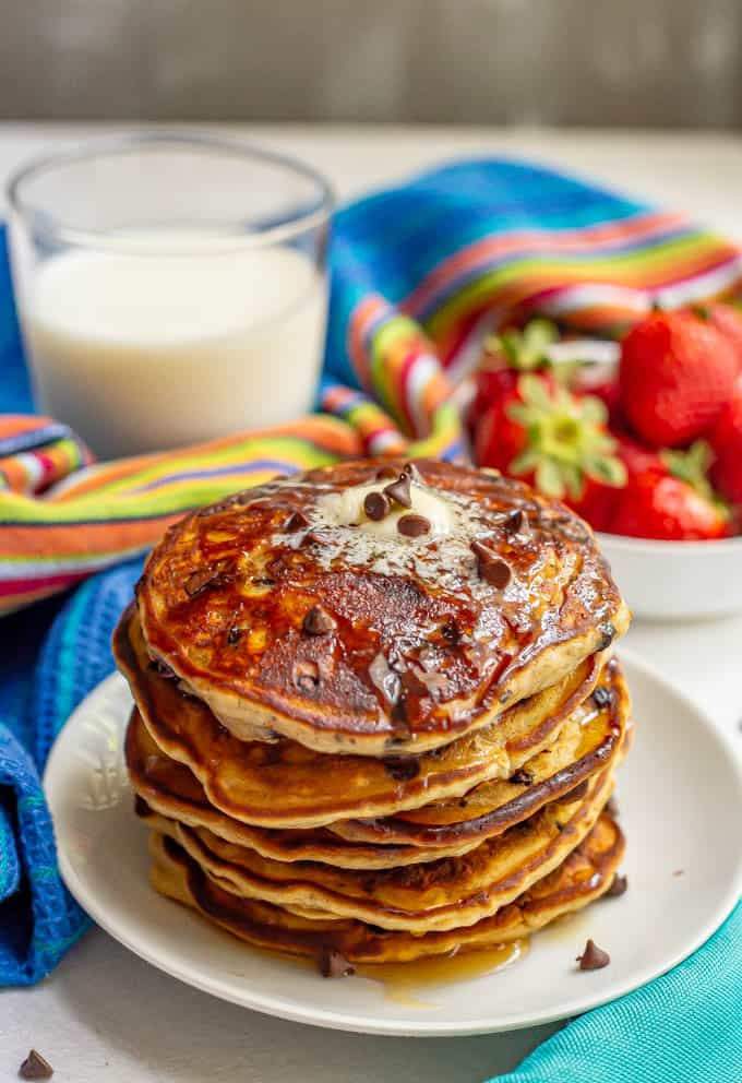 Stack of chocolate chip pancakes with butter and maple syrup served with milk and strawberries