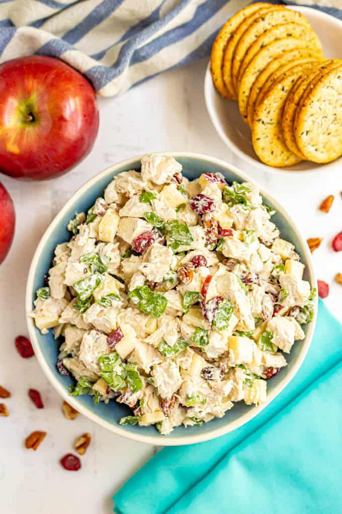 A serving bowl full of harvest chicken salad with apples, pecans, dried cranberries and spinach and crackers and apples nearby