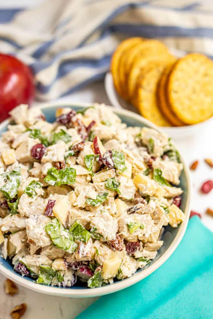 A serving bowl full of harvest chicken salad with dried cranberries and apples and spinach