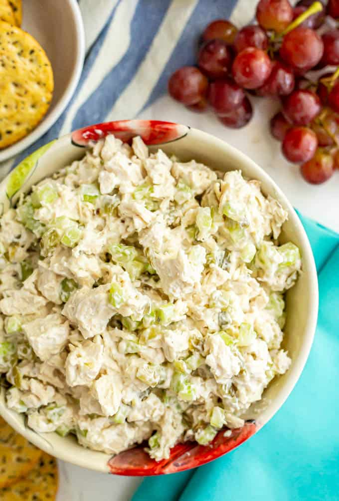 A bowl of chicken salad with a bunch of red grapes nearby