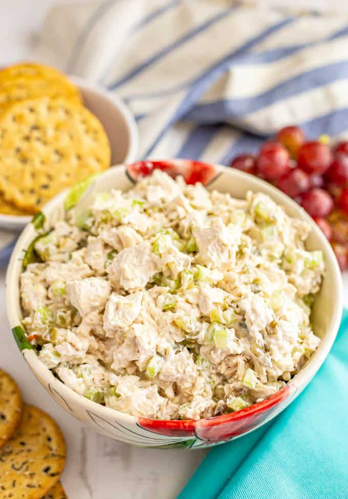 Classic chicken salad served in a bowl with crackers and grapes
