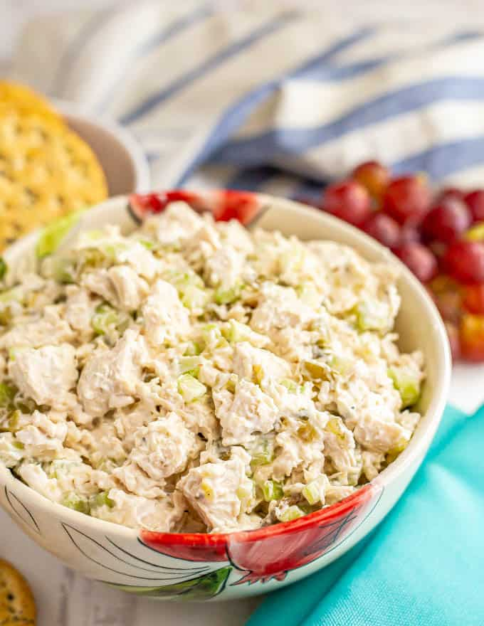 Classic chicken salad recipe served in a bowl with crackers and grapes