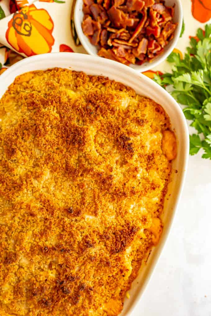 A baked casserole of macaroni and cheese with a bowl of bacon and parsley nearby