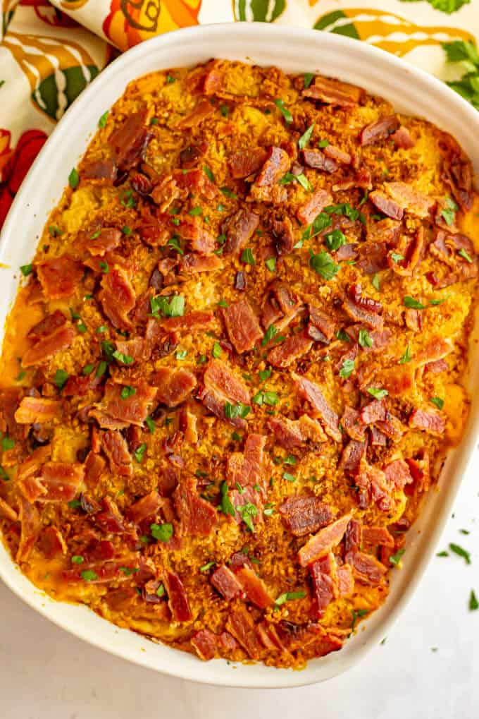A large white casserole of pumpkin macaroni and cheese with crumbled bacon on top after baking