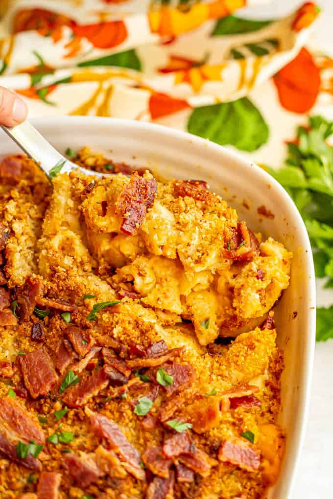A scoop of pumpkin baked mac and cheese with bacon being taken out of a white casserole dish